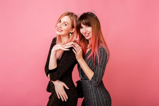 Paar prachtige vrouwen met stijlvolle jurken en kattenoren poseren