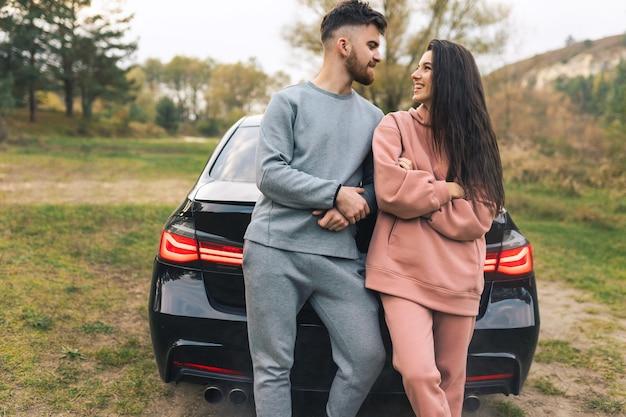 Paar praten en flirten leunend op auto