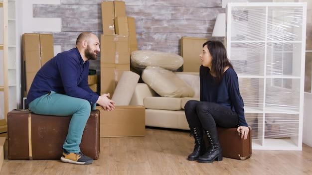 Paar praten en zitten op koffers na het dragen van dozen. kartonnen dozen op de achtergrond.
