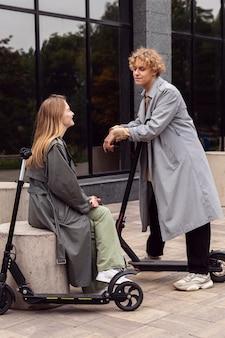 Paar praten in de stad met elektrische scooters