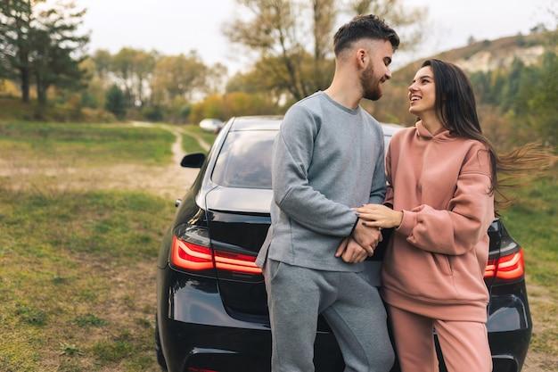 Paar praten leunend op auto