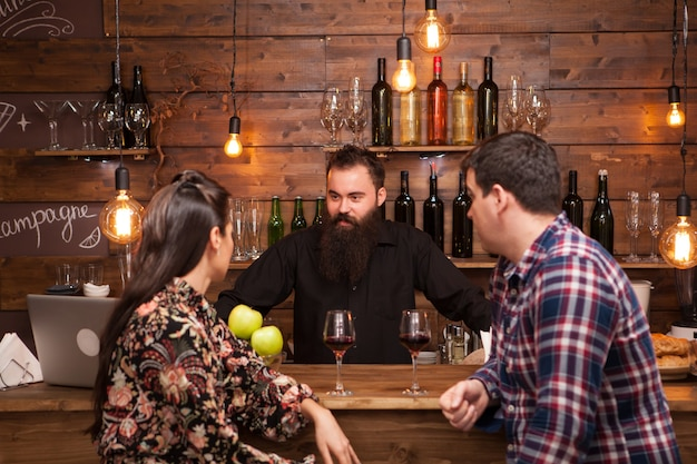 Paar praten met barman achter toog in een café. hipster-barman.