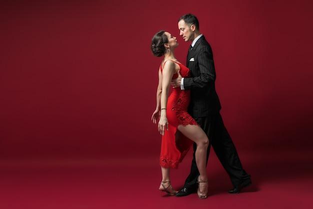 Paar professionele tangodansers in elegant pak en jurk poseren in een dansbeweging op rode achtergrond