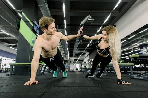 Paar pushups doen bij training in de sportschool. jong sportief paar dat samen in een gymnastiek uitwerkt. plankoefeningen doen terwijl je elkaar voor één hand vasthoudt.