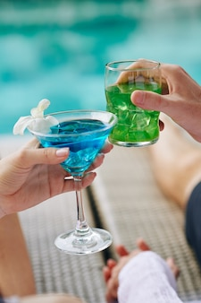 Paar rammelende glazen met cocktails