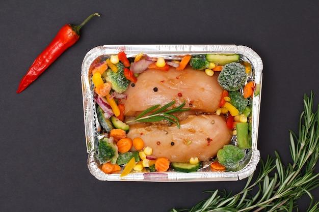 Paar rauwe kippenborsten of filet met bevroren groenten in metalen container met chili peper en rozemarijn op een zwarte achtergrond. bovenaanzicht.