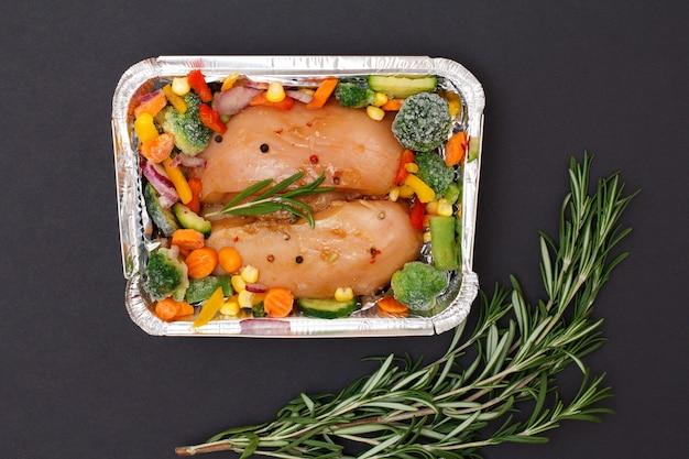 Paar rauwe kippenborsten of filet met bevroren groenten in metalen container met rozemarijn op een zwarte achtergrond. bovenaanzicht.