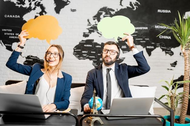 Paar reismanagers dromen met kleurrijke bubbels boven het hoofd zittend op het kantoor van het agentschap met wereldkaart op de achtergrond