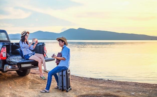 Paar reiziger hebben bagage en gitaar zittend op de auto en op zoek naar weergave van lake mounta