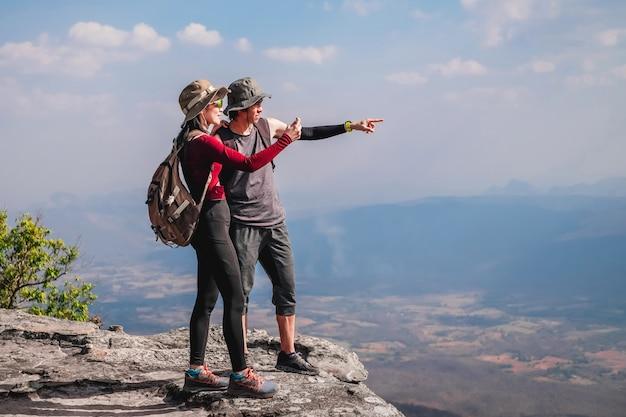 Paar reiziger zijn op de top van de berg en nemen foto uitzicht op de natuur op vakantie.