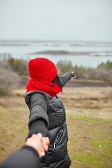 Paar reizigers hand in hand op mistig rivierlandschap