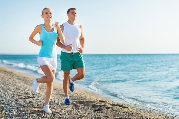 Paar rennen. sport lopers joggen op het strand lachend gelukkig uit te werken.