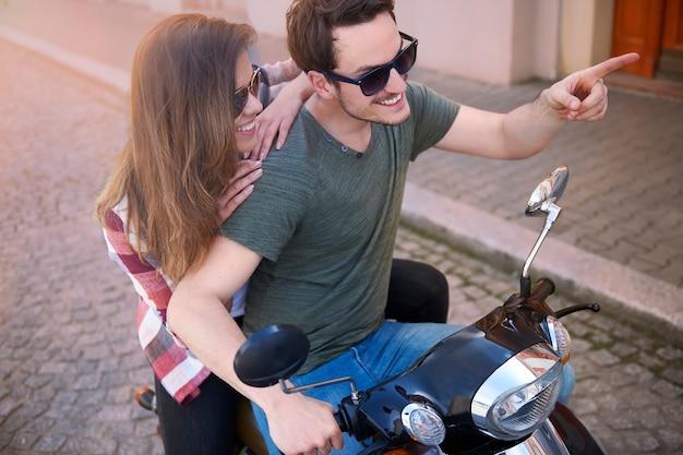 Paar rijden op een motorfiets in de stad