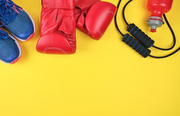 Paar rode bokshandschoenen en blauwe sneakers