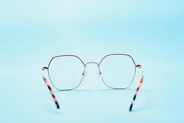 Paar rode brillen met plastic montuur op een blauwe achtergrond