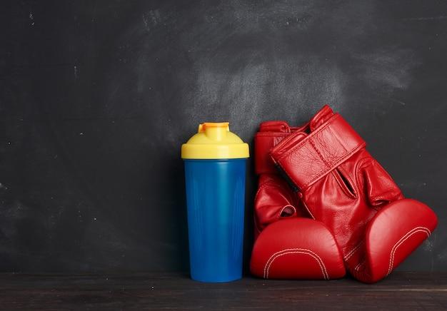 Paar rode lederen bokshandschoenen en blauwe plastic fles