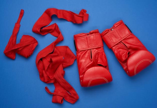 Paar rode leren bokshandschoenen en een rode elastische bandage van textiel voor de handen