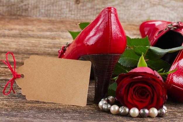 Paar rode schoenen met roze bloem en vrouwentoebehoren, exemplaarruimte op document nota
