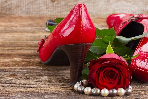 Paar rode schoenen met roze bloem en vrouwentoebehoren op houten achtergrond