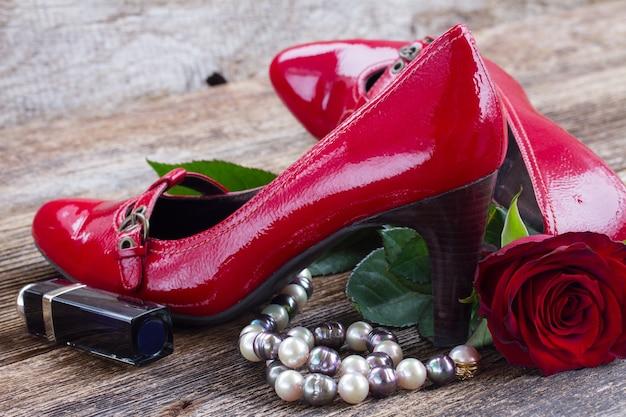 Paar rode schoenen met rozen- en pareljuwelen op hout
