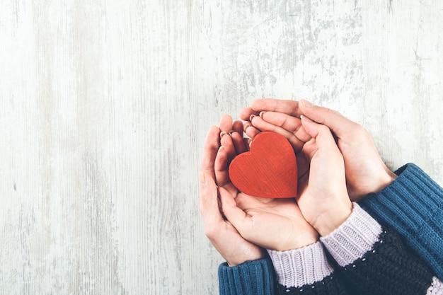 Paar rood hart op houten oppervlak te houden