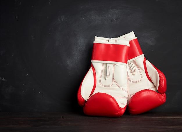 Paar rood-witte leer bokshandschoenen op een zwarte achtergrond, sportuitrusting