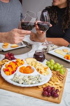 Paar roosteren met wijn en kaas tijdens het diner. focus op kazen