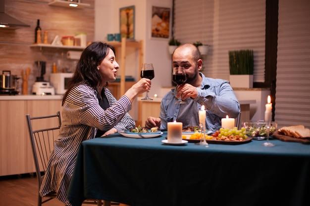 Paar roosteren met wijnglazen tijdens romantisch diner. ontspan gelukkige mensen die rammelen, aan tafel zitten in de keuken, genieten van de maaltijd, jubileum vieren in de eetkamer.