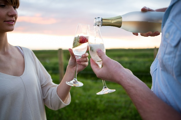 Paar roosterende champagne in veld
