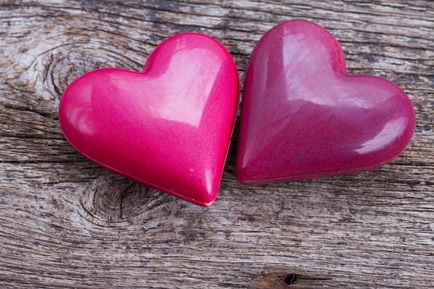 Paar roze harten die samen op houten achtergrond leggen
