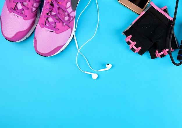 Paar roze sneakers met veters op blauw