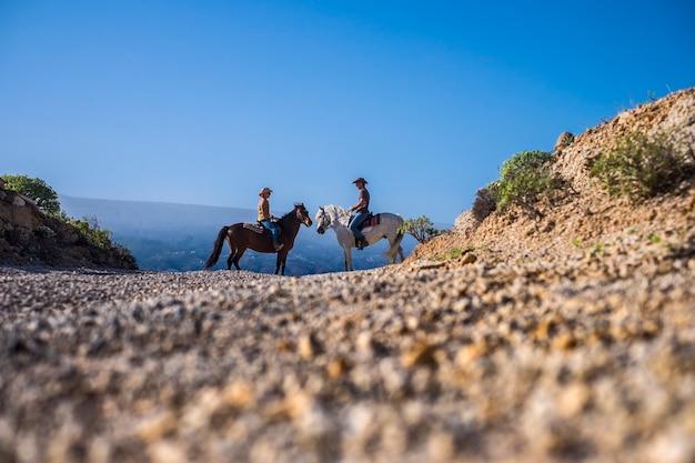 Paar ruiters met paarden wit en bruin kijken en blijven samen vooraan in het midden van de compositie.
