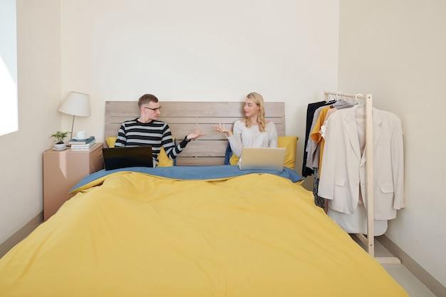 Paar rusten in bed met laptops en vragen elkaar om wat hapjes en drankjes mee te nemen in de slaapkamer