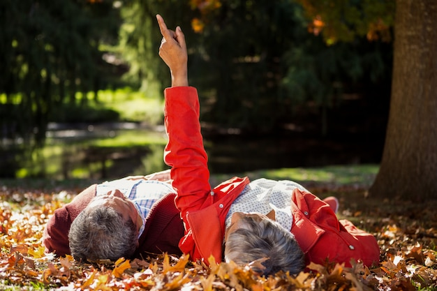 Paar rusten op herfstbladeren