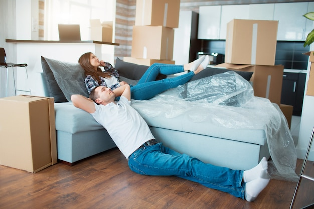Paar rustend op de bank na het verhuizen, man en vrouw ontspannen op de bank net verhuisd naar appartement met kartonnen dozen op de vloer, tevreden tevreden huiseigenaren genieten van de eerste dag in een nieuw huis