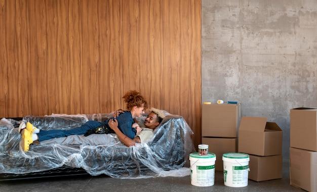 Paar rustend op een bank in hun nieuwe huis naast verfemmers