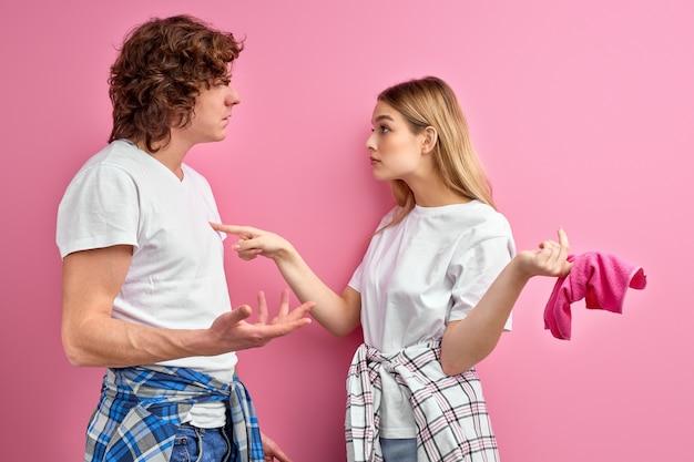 Paar ruzie vanwege huishoudelijke taken. vrouw is ongelukkig met het niets doen van haar man tijdens het schoonmaken thuis Premium Foto
