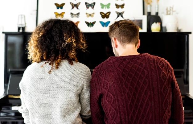 Paar samen oefenen op een piano