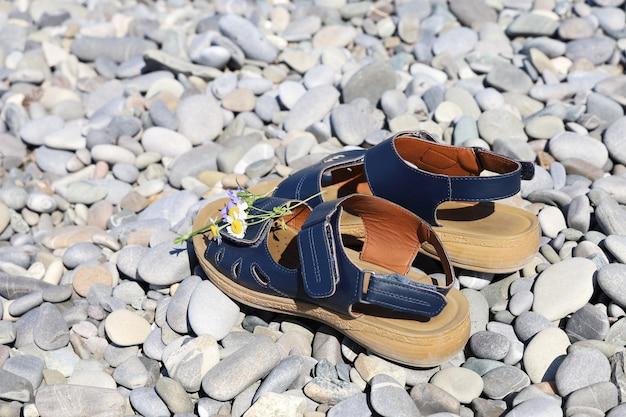 Paar sandalen met kleine wilde bloemen bovenaan, op kiezeloppervlak zonder mensen