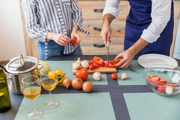 Paar scherpe groenten op houten plank aan tafel