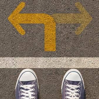 Paar schoenen die zich op een weg met bidirectionele gele pijl bevinden