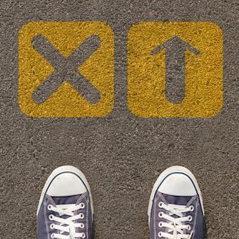 Paar schoenen die zich op een weg met gele pijl twee bevinden
