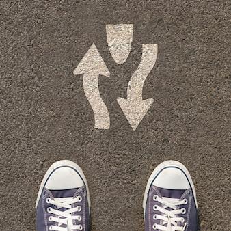 Paar schoenen die zich op een weg met verkeersteken bevinden