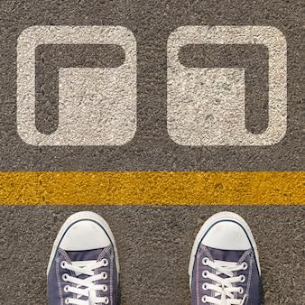 Paar schoenen die zich op een weg met witte pijl twee bevinden