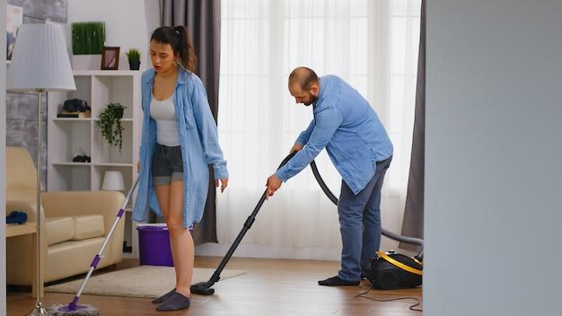 Paar schoonmaken van de vloer met behulp van dweil en stofzuiger. Premium Foto