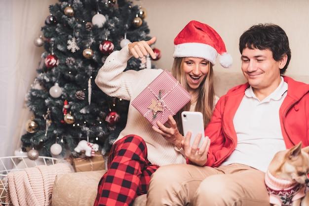 Paar schuren kerstgroeten met hun smartphone