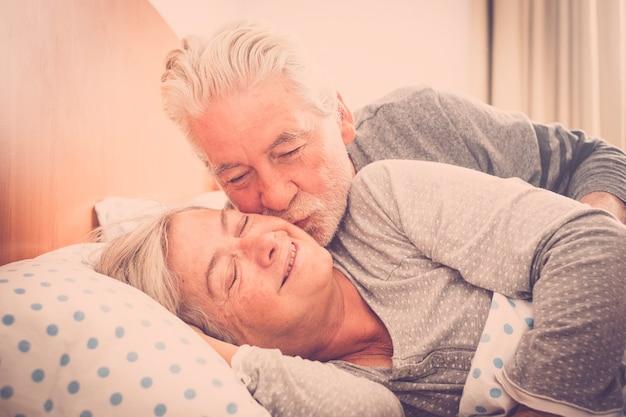 Paar senior blanke man en vrouw zoenen in de vroege ochtend aan het bed thuis voor liefde elke dag zonder limiet leeftijd - eeuwigheid samen concept voor gelukkige vrolijke mensen getrouwd in relatieshi