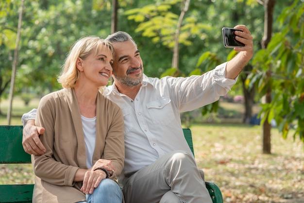 Paar senior selfie foto samen zittend ontspannen op bankje in park