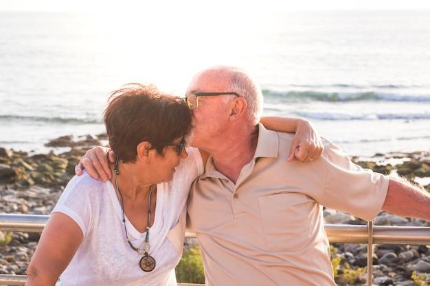 Paar senioren die met veel liefde op het strand zitten - samen met pensioen - vrouw met bril en man met zeeachtergrond - haar kussen