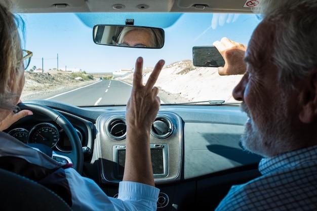 Paar senioren en gepensioneerden in de auto rijden en nemen een selfie samen glimlachend en kijkend naar de camera